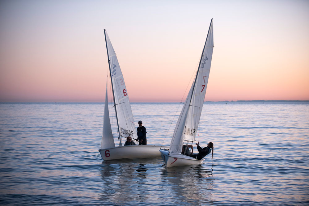 The UConn sailing club sailing in Long Island Sound during sunset at the Avery Point campus